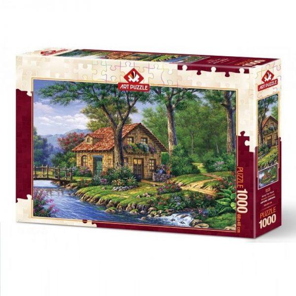 """Puzzel """"Along the piece"""" met afbeelding van huisje aan een beek."""